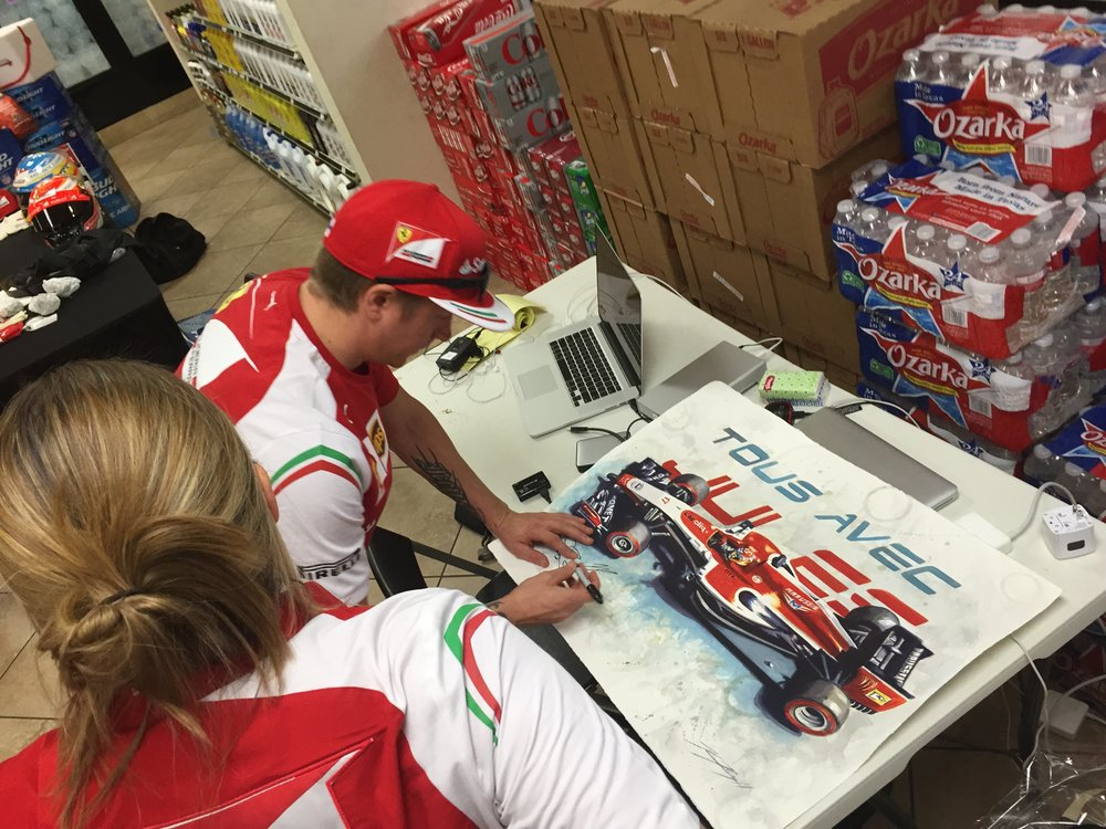 Kimi signing a tribute painting 'With You' of Jules Bianchi at the USGP