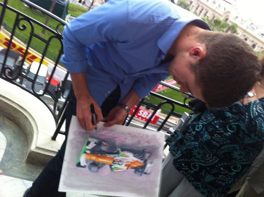 Paul di Resta autographing a KPA piece