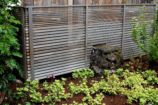 The boulder and screen combo provides a backdrop for native plantings.