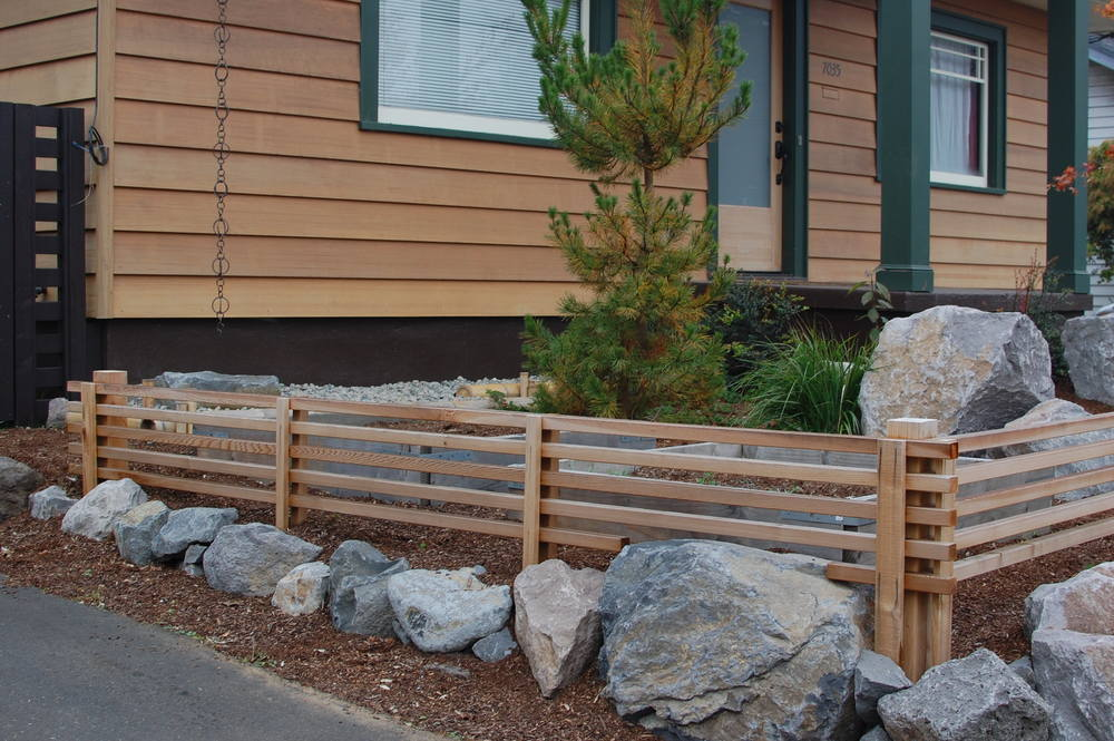 Retaining along one property line is topped with cedar screening.