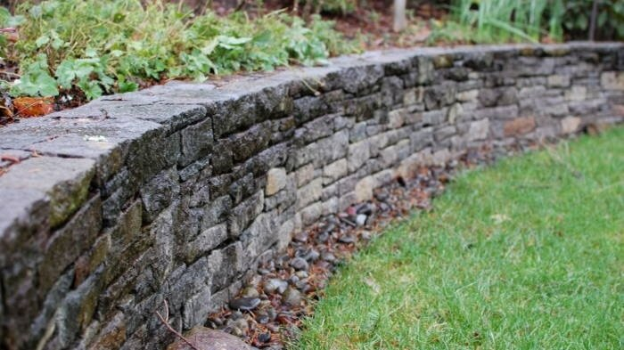 "Curved  retaining wall . Avison basalt is used in the ""Ashlar"" style to create a beautiful wall. This wall is just stone and mortar."