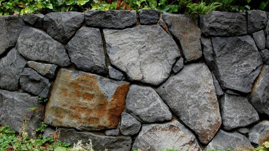 Basalt boulder retaining wall with deeply recessed joints.