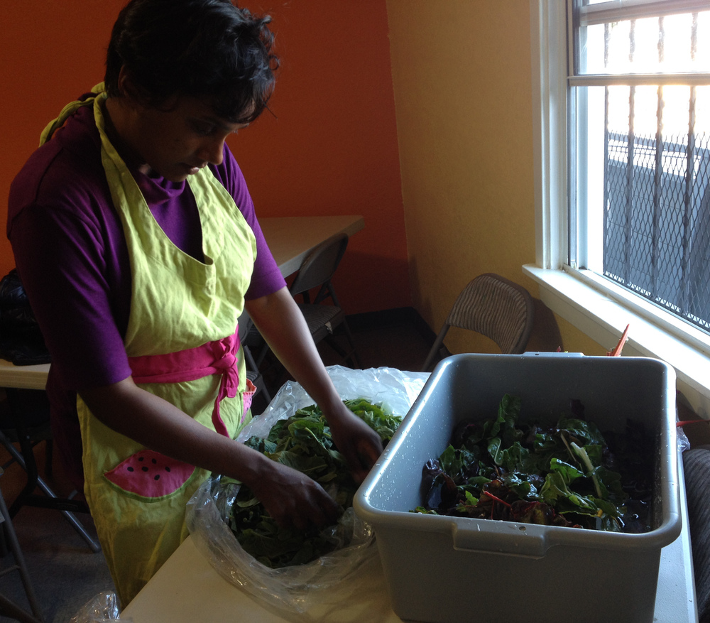 Monica prepping salad greens donated by FarmBox SF for the Feeding Portrero Healthy Catering Team.