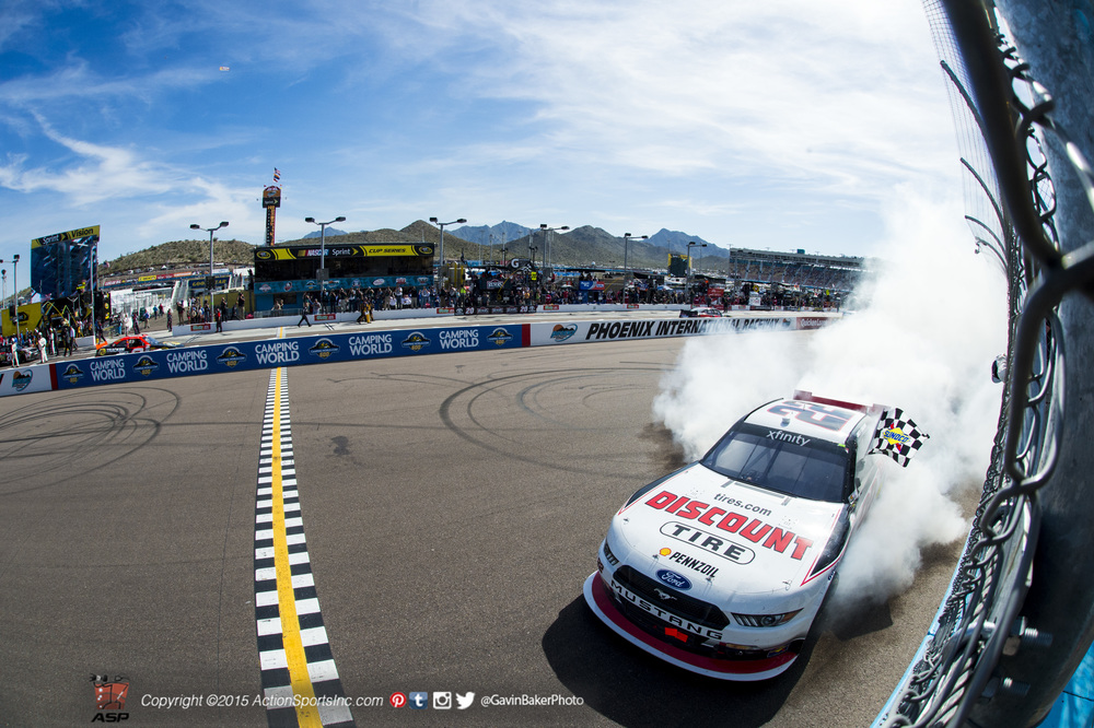 Joey Logano  collects the checkered flag as he does a burnout along the front stretch after winning the Axalta 200 Xfinity series race at Phoenix International Raceway in Avondale , AZ.