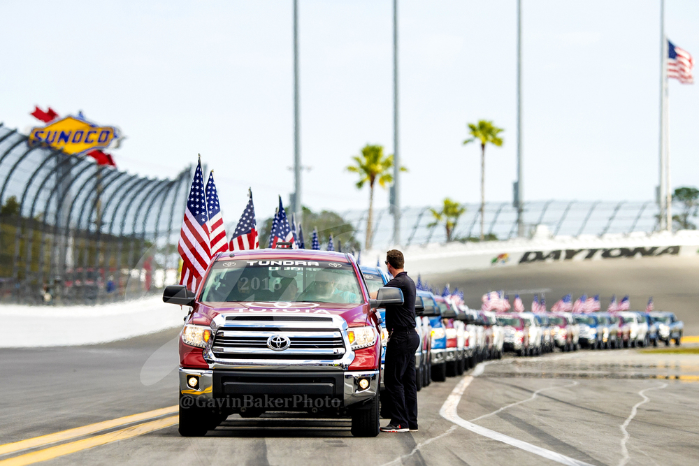 The line of Toyota Tundras wait for the signal to pick up the drivers after they have been announced for a parade lap around Daytona