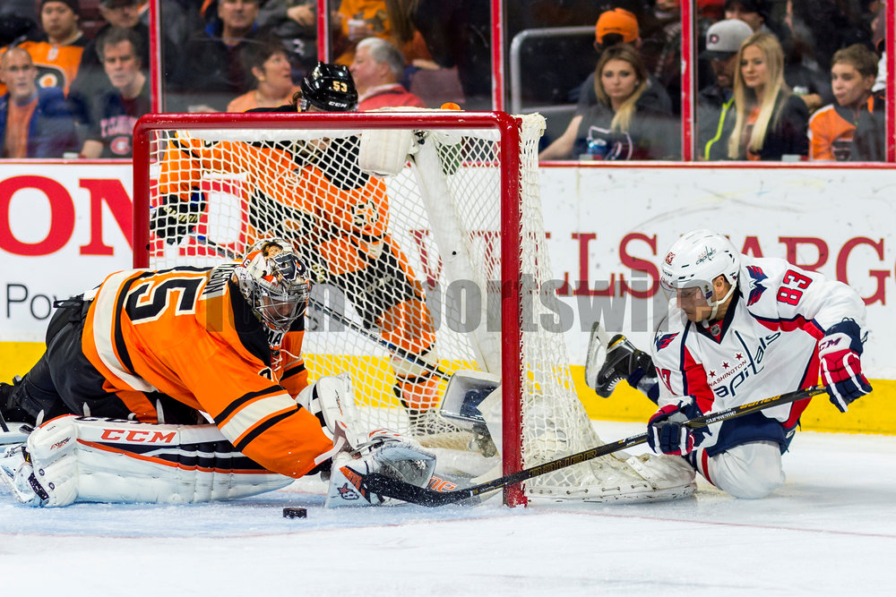 30 March 2016: Washington Capitals center Jay Beagle (83) dives and shoots around the net as Philadelphia Flyers goalie Steve Mason (35) makes the save during the NHL game between the Washington Capitals and the Philadelphia Flyers played at the Wells Fargo Center in Philadelphia, PA. (Photo by Gavin Baker/Icon Sportswire)
