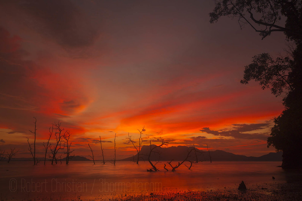 Beautiful sun setting behind the Santubong peninsula seen from Bako National Park.