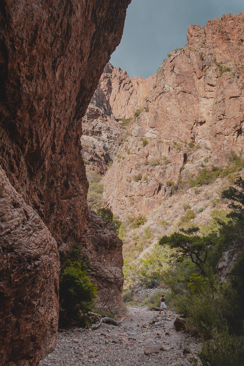 woman walking though canyon with vertical walls