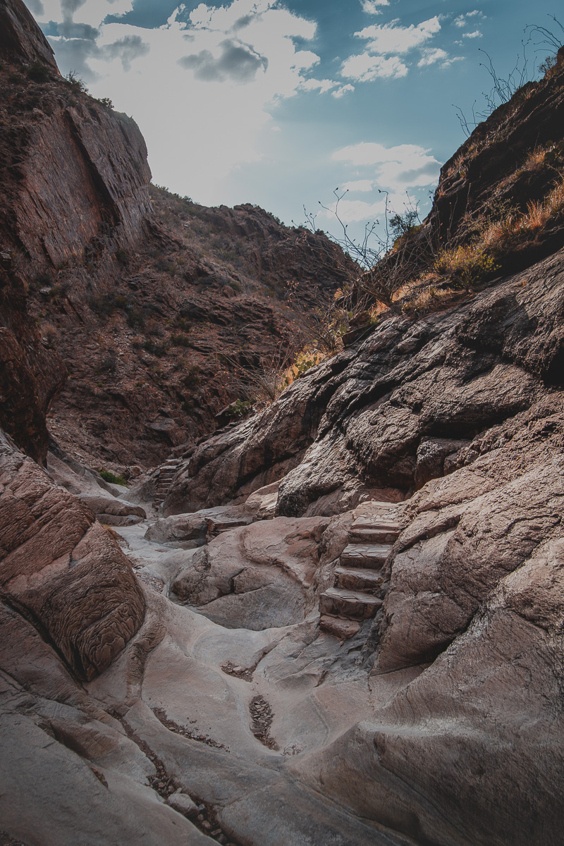 empty swimming hole naturally carved into rock formation in canyon