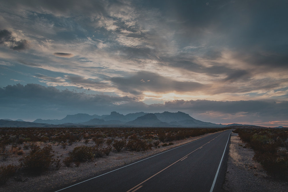 paved road leading towards mountains with sun setting behind them