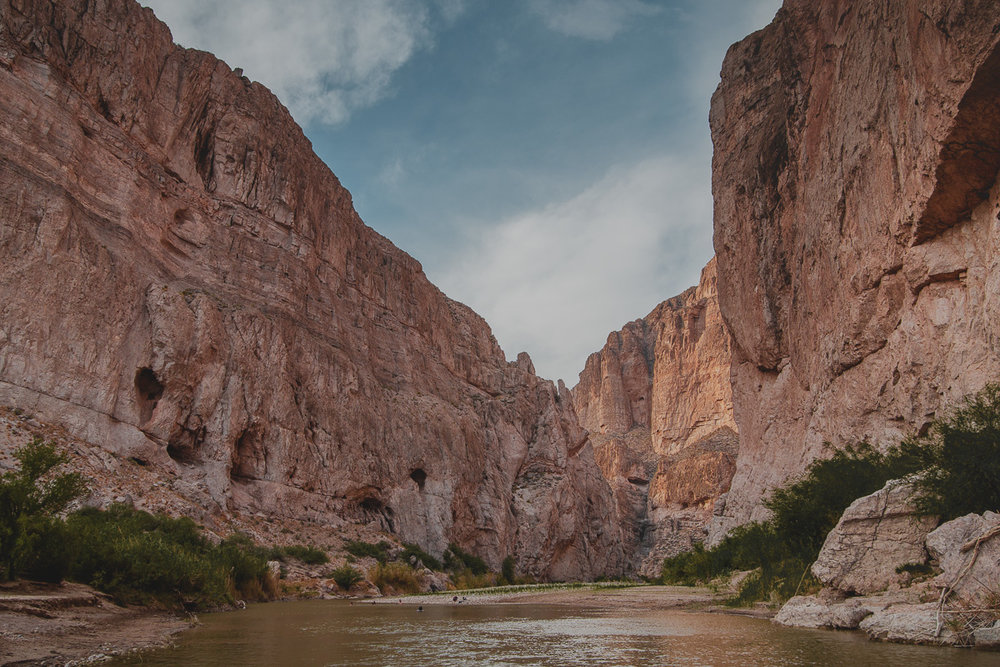 people swimming in river running through steep canyon on border of mexico and united states