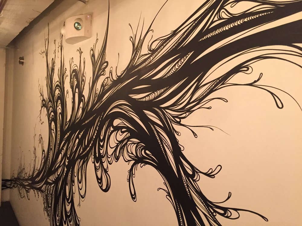This project was commissioned by Timothy Felkner who opened up the short lived Oro restaurant during summer 2015 in Mint Plaza. The main motivation here was to create a sweeping piece of art that encapsulated all sides of a subterranean hallway which leads diners to the restrooms in the basement of the building.  During the design phase I was struck that the work space was underneath the streets and buildings of San Francisco. I felt the power of being INSIDE the city. I was reminded of the 1906 earthquake and the energy that lies dormant underground. I thought of the nutrients in the Earth which gives rise to the food that grows from it. This two ideas harmonized and became the swirling sprouting mural that emerged.   When I began this project the area had a dull, bland industrial feel with no life to it. Afterward, I created a one of a kind art piece which was an interpretation of what it's like for life to emerge from deep inside the city.