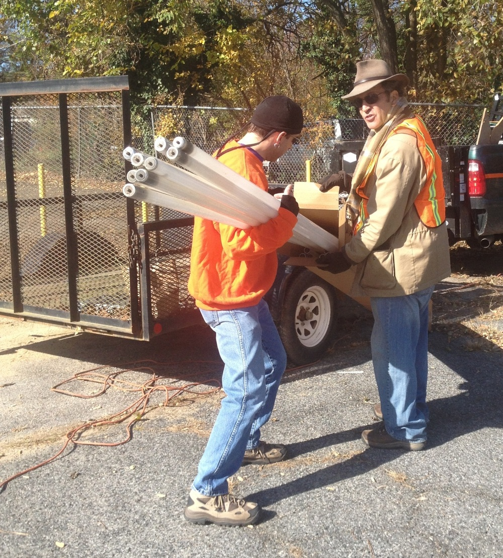 "Nathan Guinn (L.)  and Blair Pollock of Orange County Solid Waste Management load a box full of burned out fluorescent lamps brought over by Ryan Richardson of CD Alley for recycling at the first-ever ""Electro Junk Dump"" event held November 17 in downtown Chapel Hill."