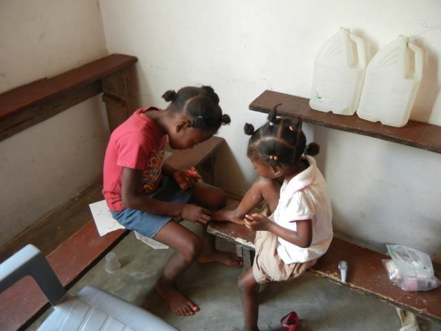 Haitian girls painting each other's toenails.
