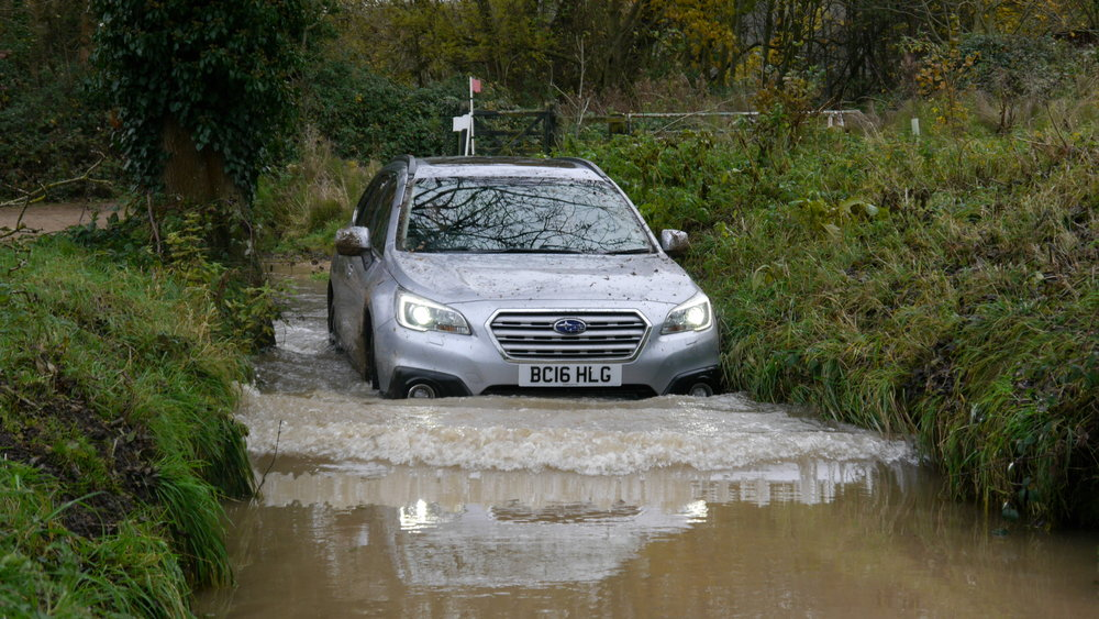 Andrew narrowly avoids planting a Subaru Outback in a riverbank. From the river.