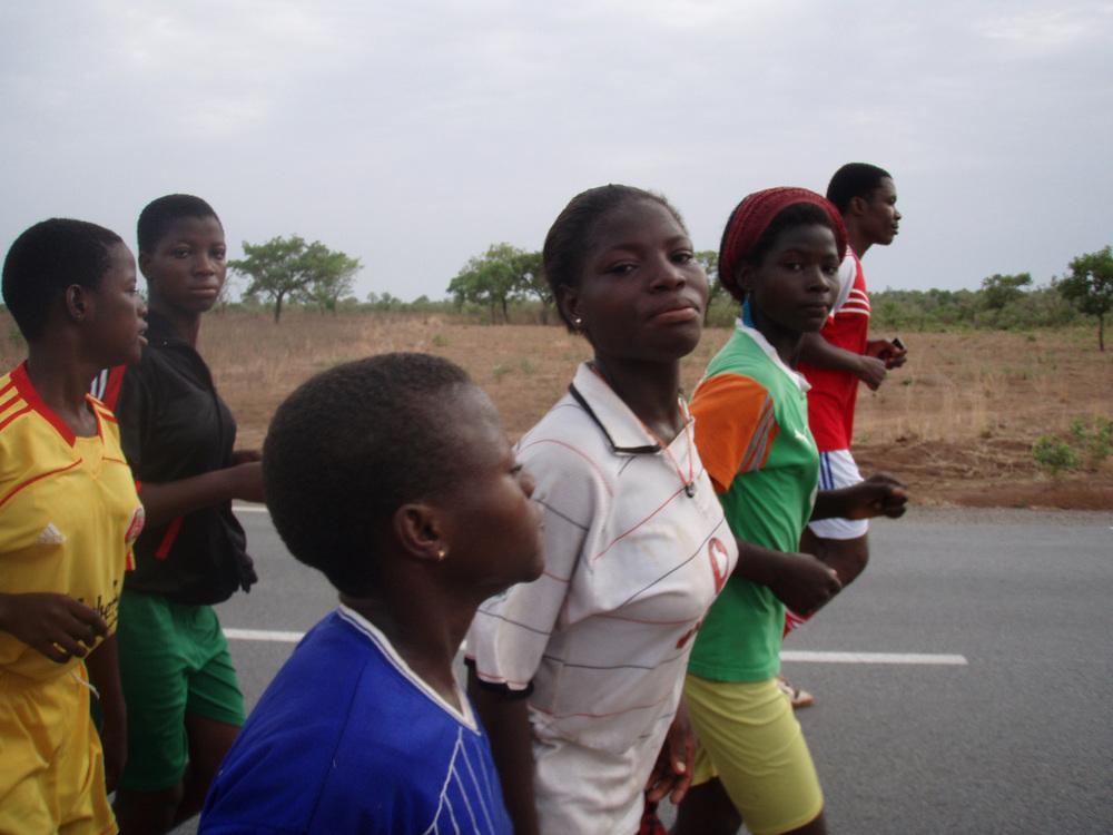 Girls run along the two-lane national highway on a Saturday morning.