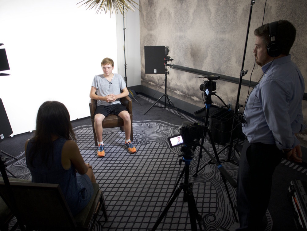 Behind the scenes interview with teenage man on a white seamless backdrop