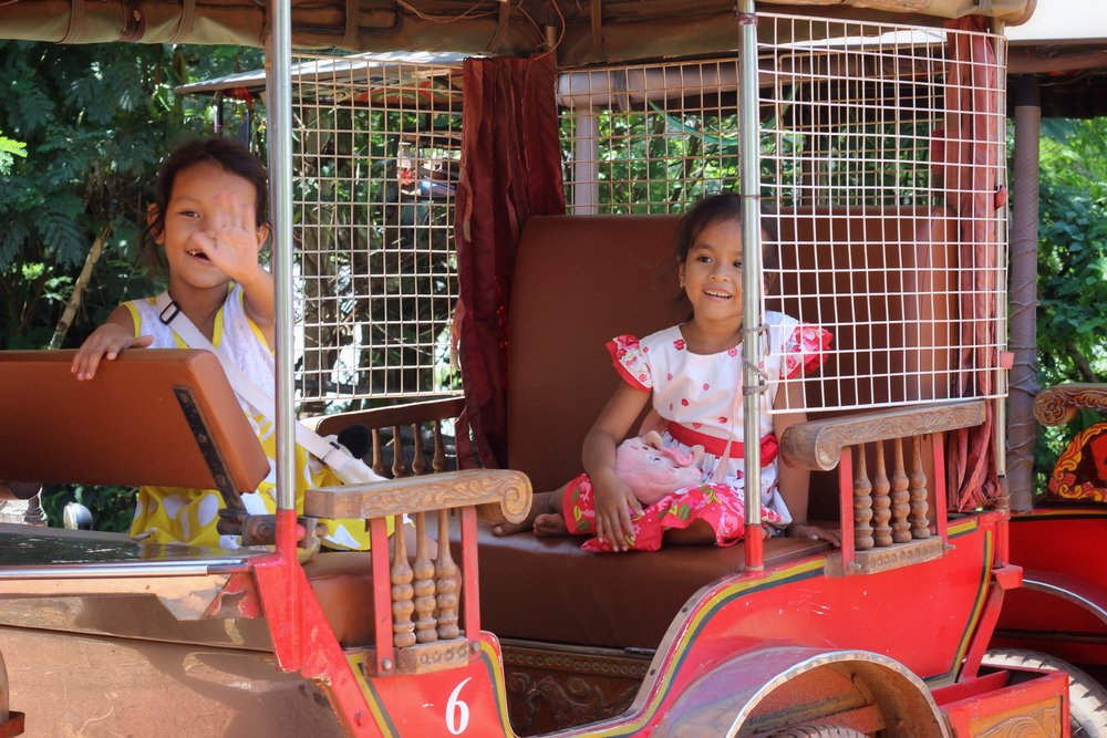 Local girls waving hello from a resting tuk tuk. Children are, without fail, very excited to see foreigners.