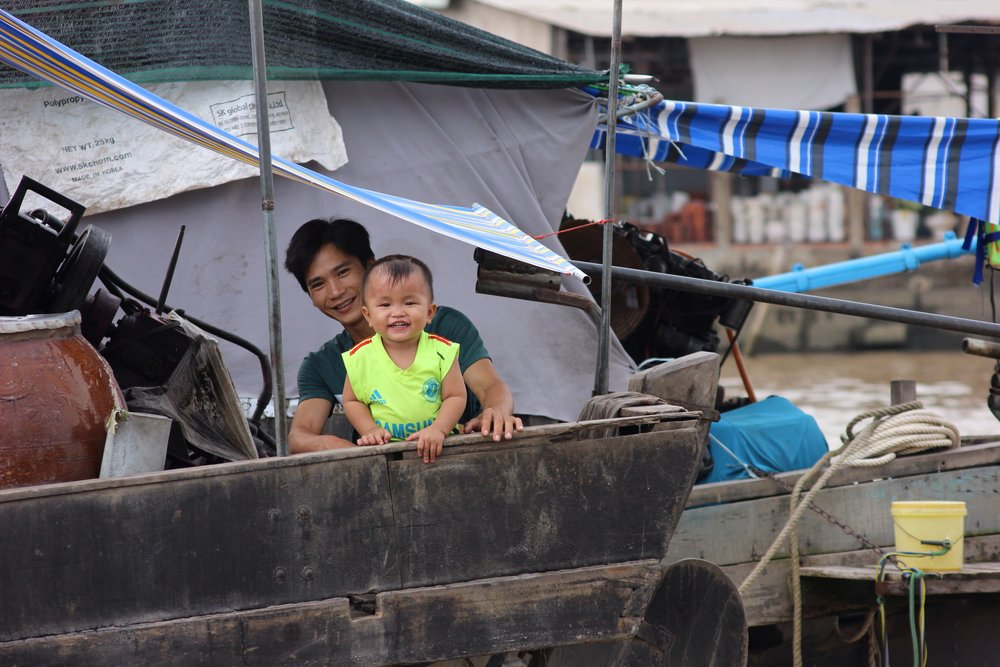 A little boy grins at us from the back of a vendor's boat at the floating market. These boats have long bamboo poles on which they hang examples of what they're selling. (Although a hat affixed to the pole means that the boat is for sale).