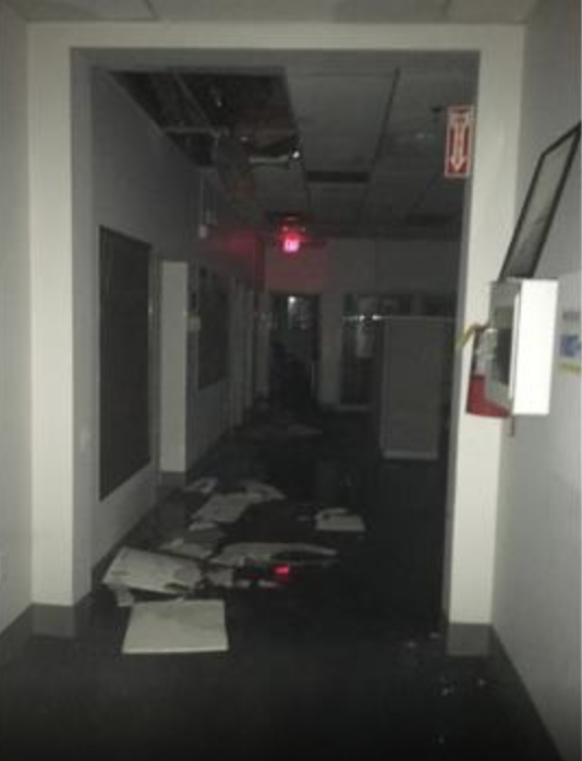 Ceiling tiles have fallen as water enters the building.