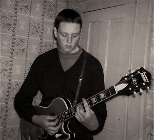 A young Top strumming the guitar in 1963