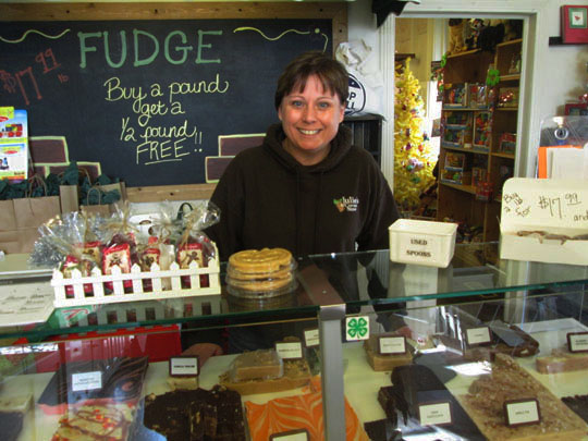 Julie stands behind the ever-popular glass counter of tasty, homemade fudge in the front room.