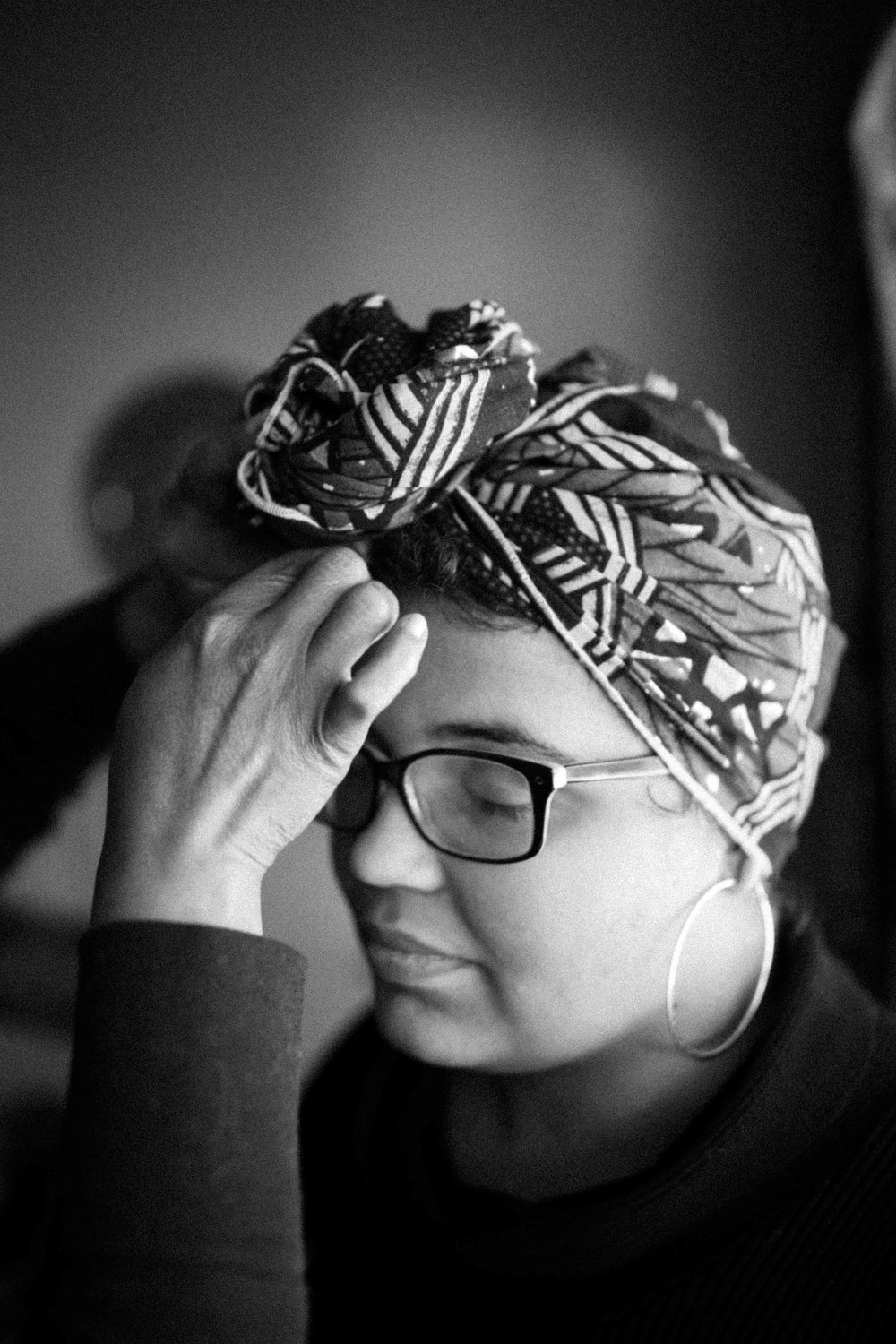 "Alexis having her head wrapped, an act of honor to ancestors and cultural reclamation. For more on the history of the head-tie, see "" The History of Headwraps Worn by Women of Color ,"" and the work of Juliana Kasumu in   From Moussor to Tignon ."
