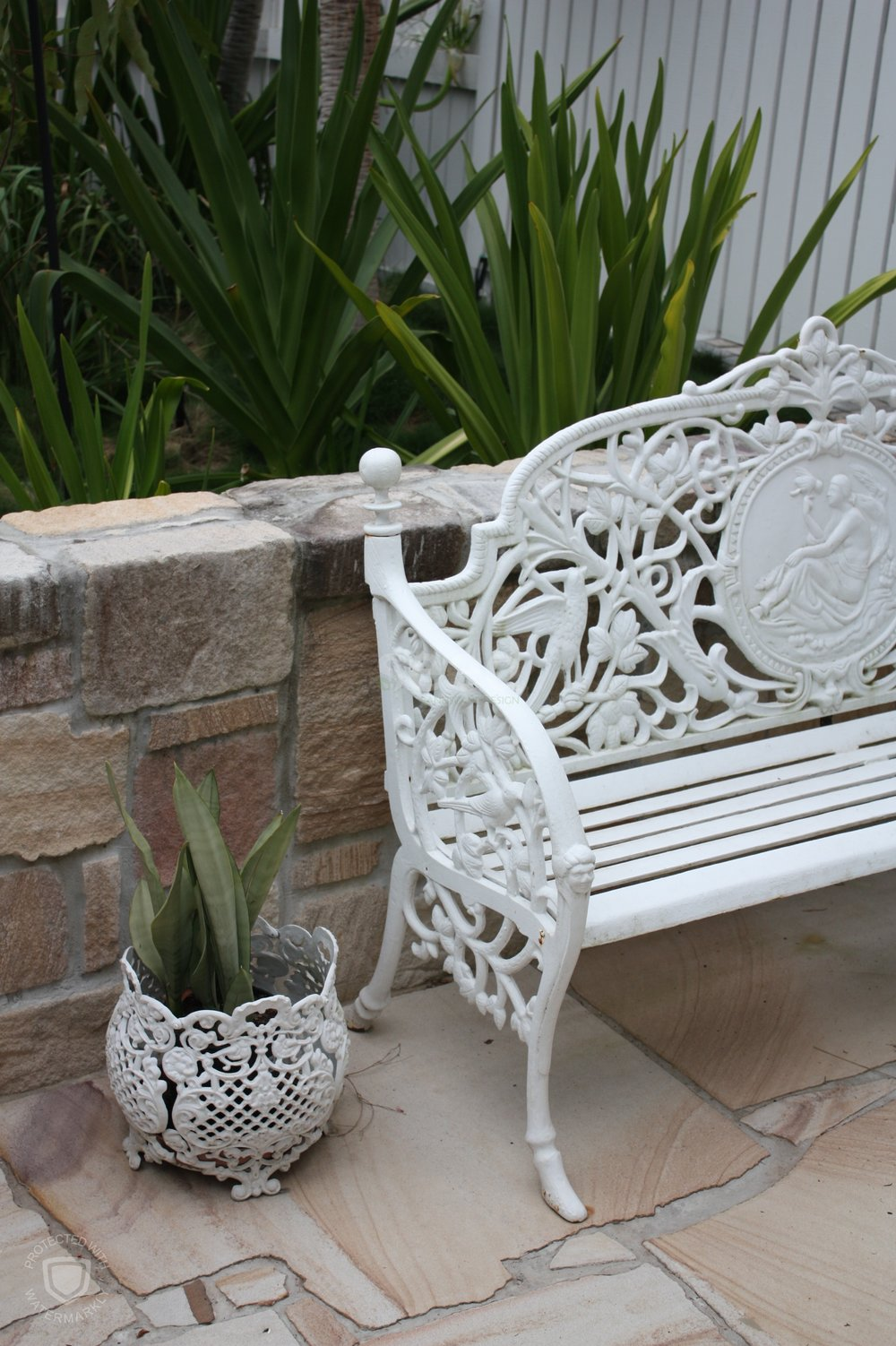 Details such as these white wrought iron pieces help to tie the white slates with the sandstone features.