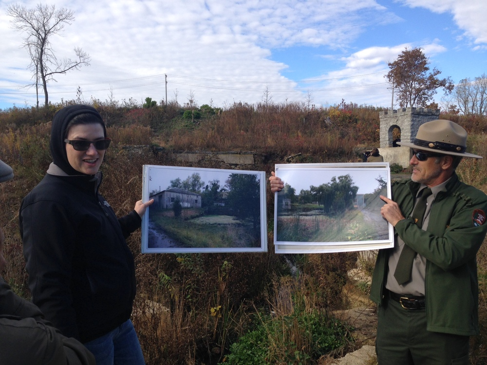 Collaboratory Scientist Kate Brauman helps Alan hold photos of the site as it was prior to recent restoration.