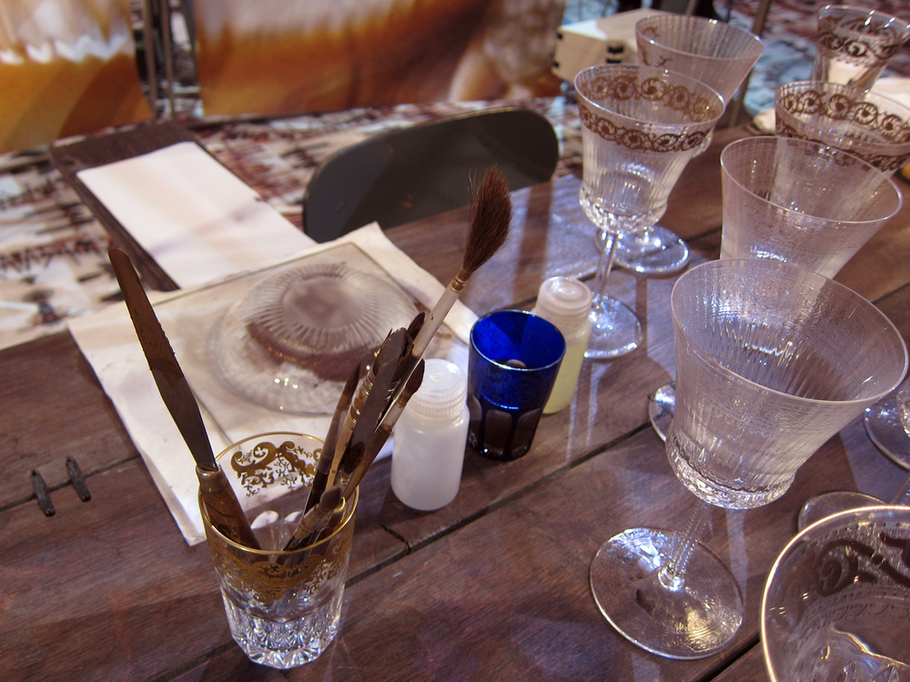 The master gilder's tools set next to stemmed glasses being prepared for their gold.