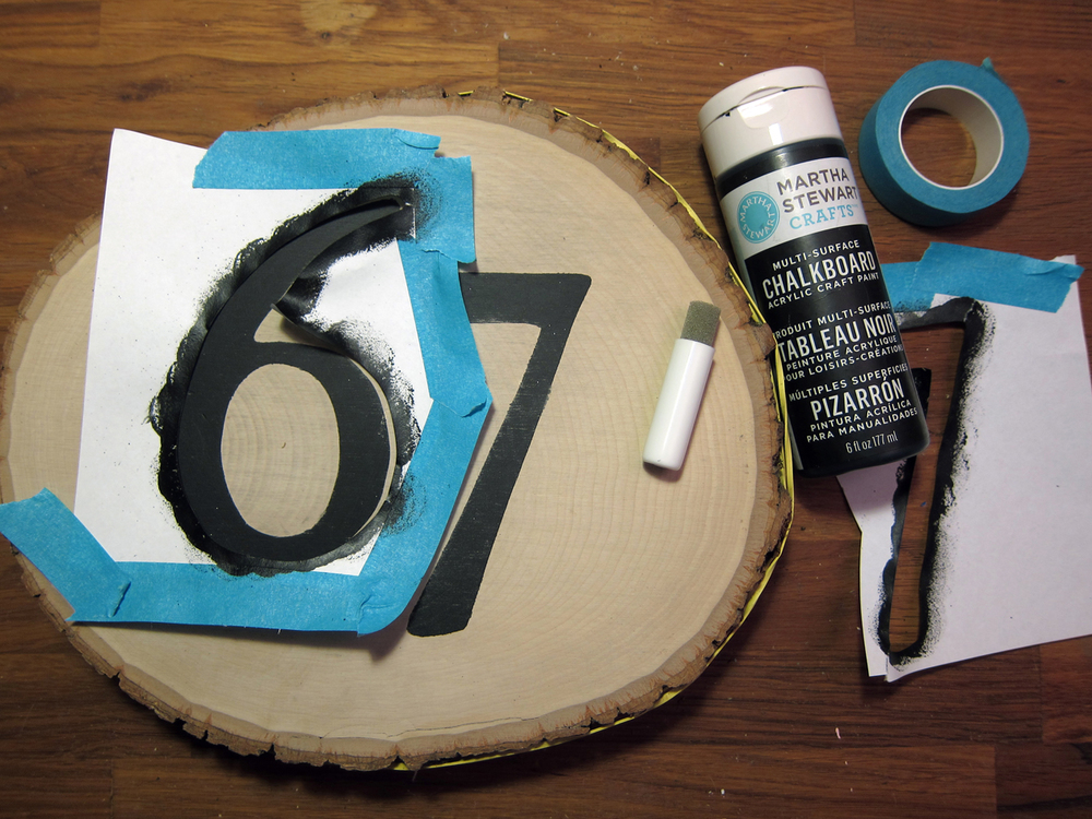 Create a number stencil. Pick a font and print out numbers to a piece of paper in the appropriate size. Cut numbers out with utility knife on a cutting mat. Save all number elements (i.e. inside circle of number 6).  Position and center stencil to front of basswood round. Secure with tape.  With paint and a foam pouncer, stencil the number. Remove paper stencil and let dry.