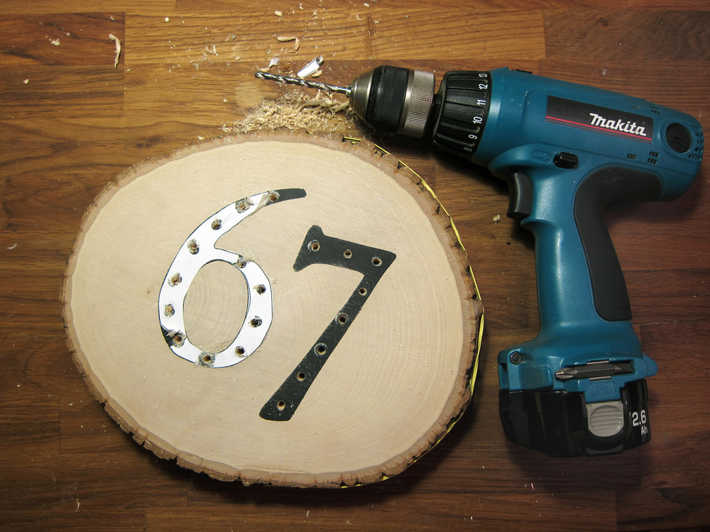 "With the numbers that were cut from stencil, evenly mark 20 light holes. Tape paper numbers over painted numbers on basswood. With a drill affixed with an 11/64"" bit, drill through basswood round on marks."