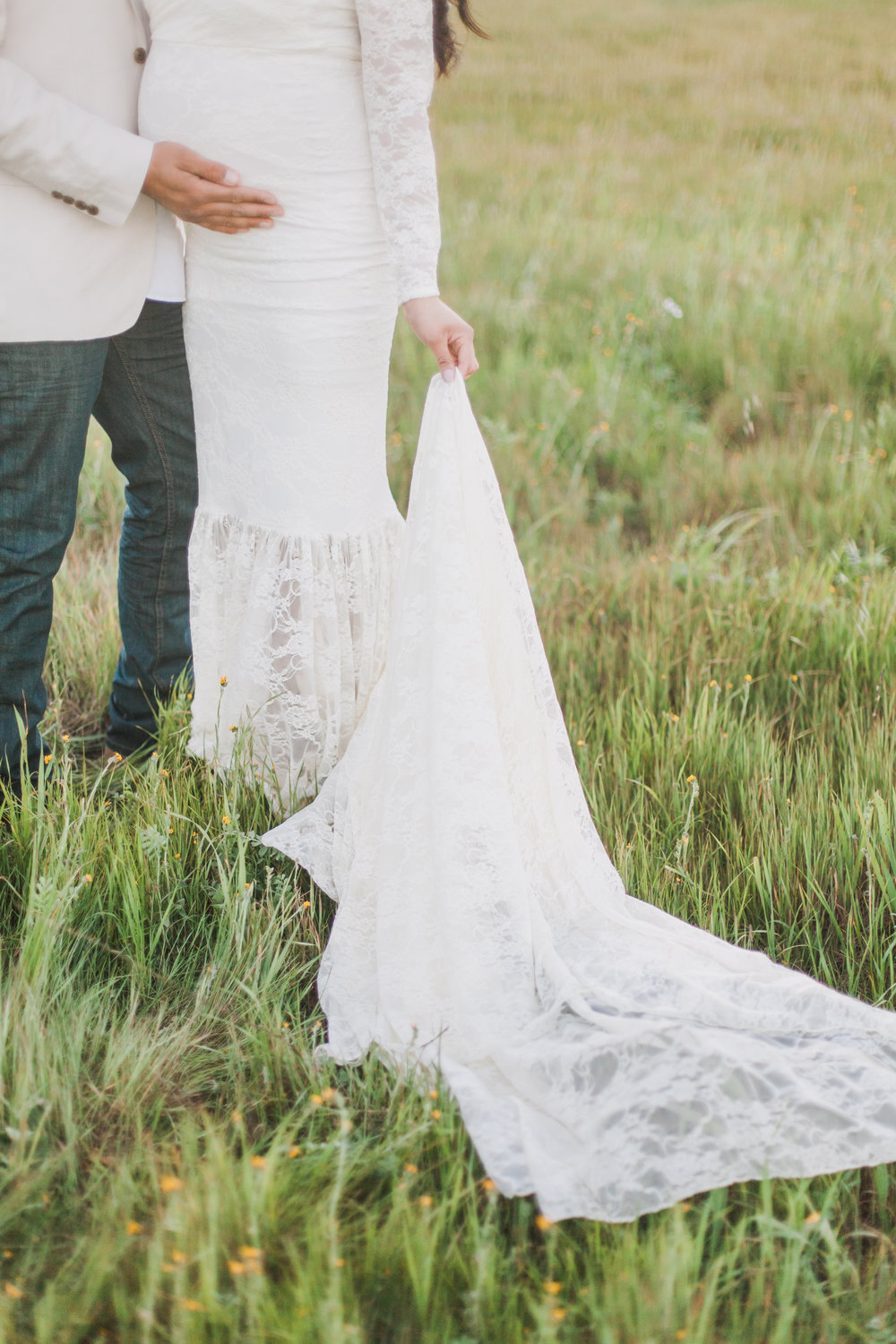 Woman holding her white vintage dress in a grass field during maternity session in San Jose, California.
