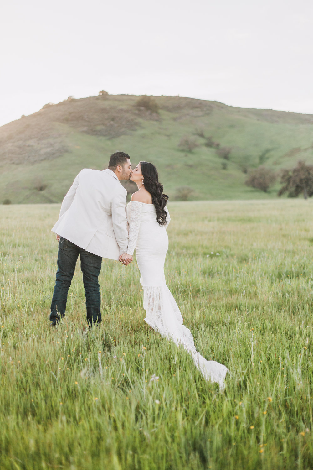 Couple kissing in grass field during maternity session in San Jose, California.
