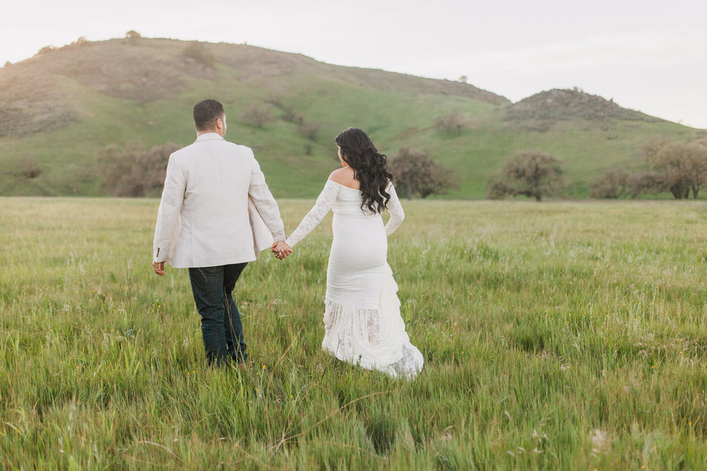 Couple walking in a grass field wearing during maternity session in San Jose, California.
