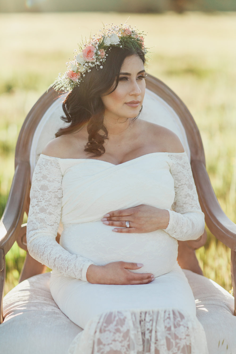 Woman sitting on vintage chair during maternity session in San Jose, California.