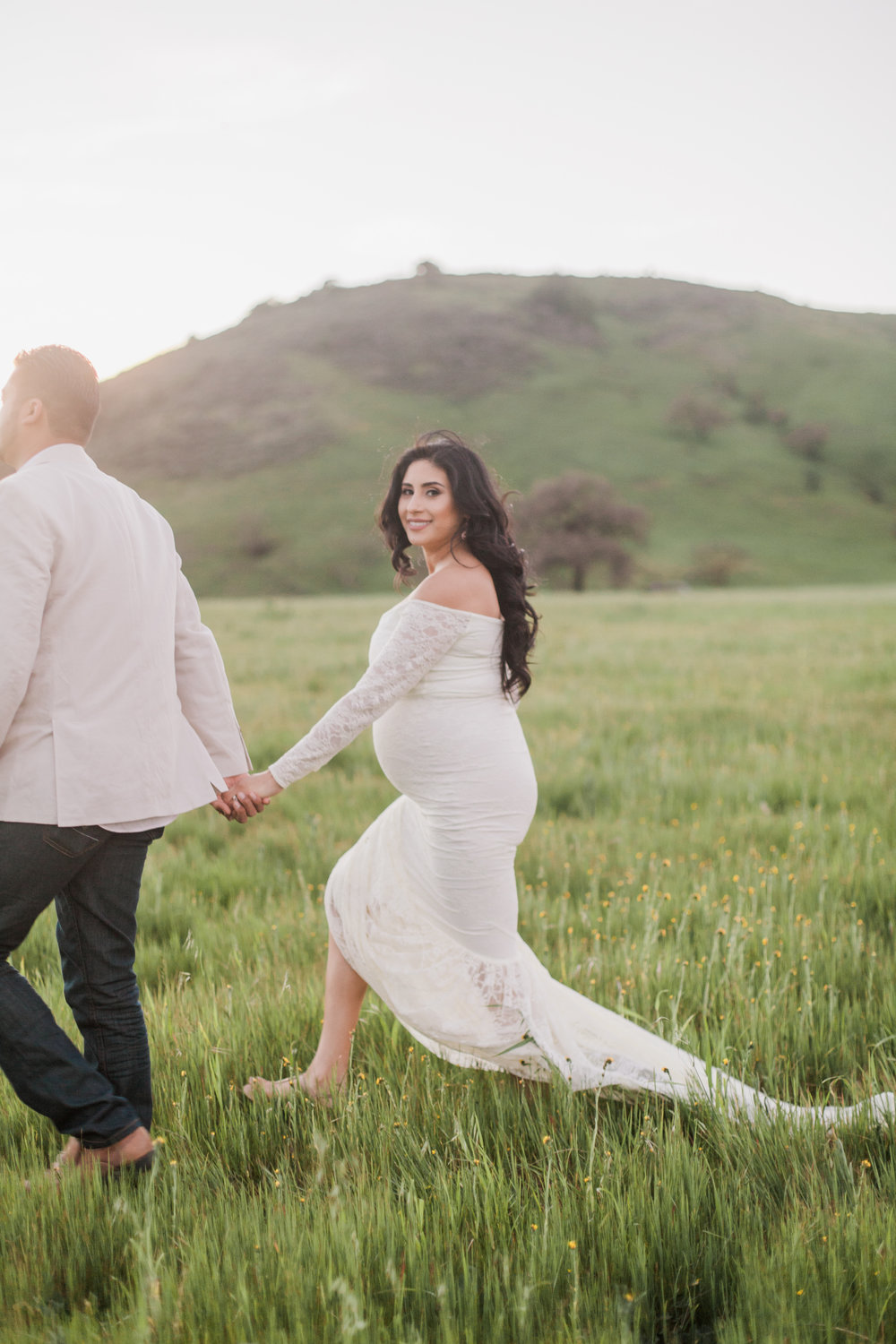 Couple walking in grass field during maternity session in San Jose, California.