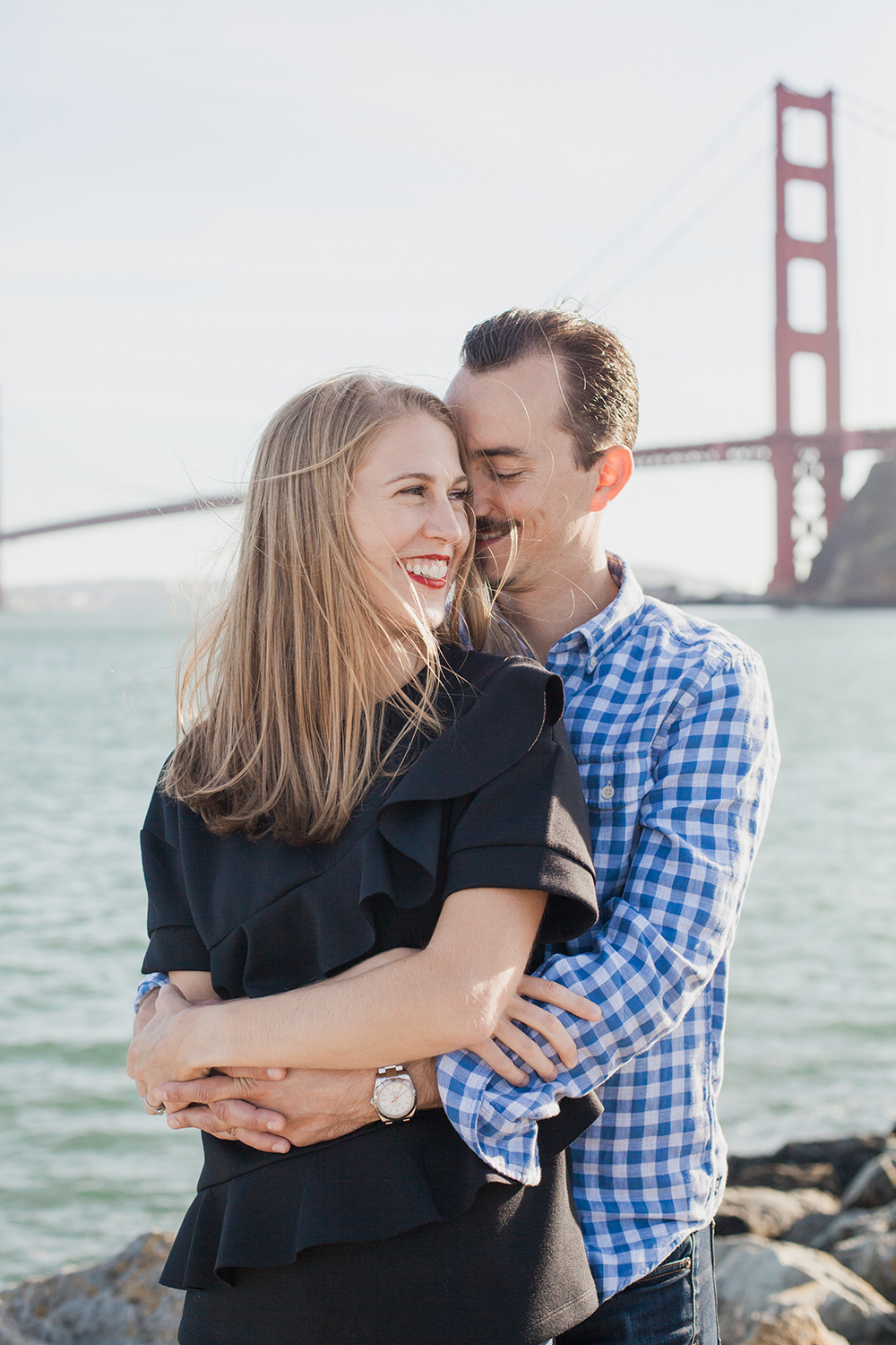 Couple hugging during their Golden Gate Bridge engagement session in San Francisco, California.