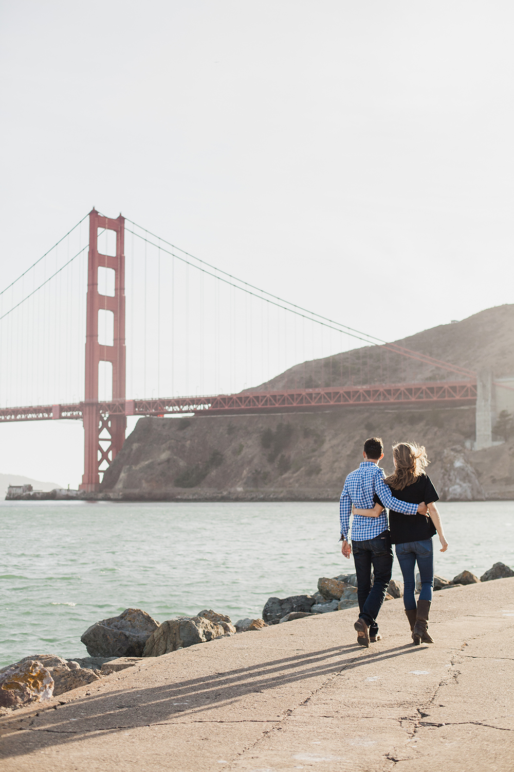 Couple walking together during their engagement session at Cavallo Point with backdrop of Golden Gate Bridge.