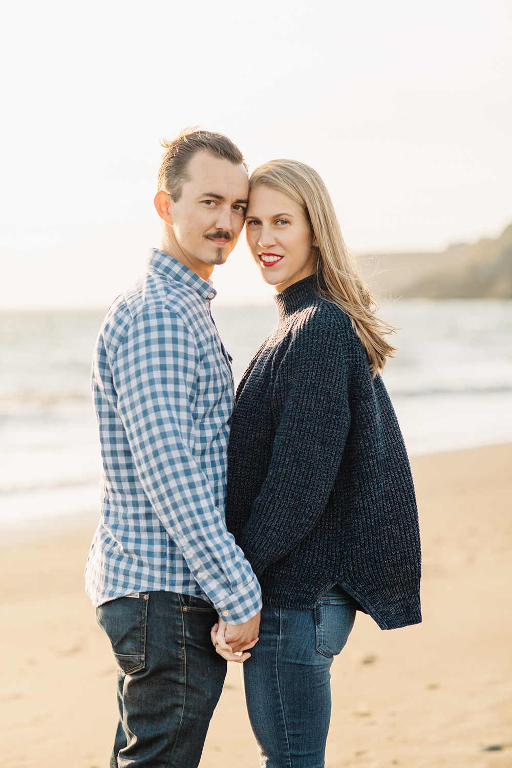 Portrait of couple during engagement session at Rodeo Beach in Marin Headlands, California.