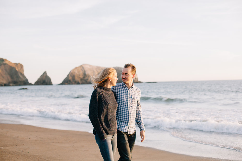 Portrait of couple walking during their engagement session at Rodeo Beach in Marin Headlands, California.