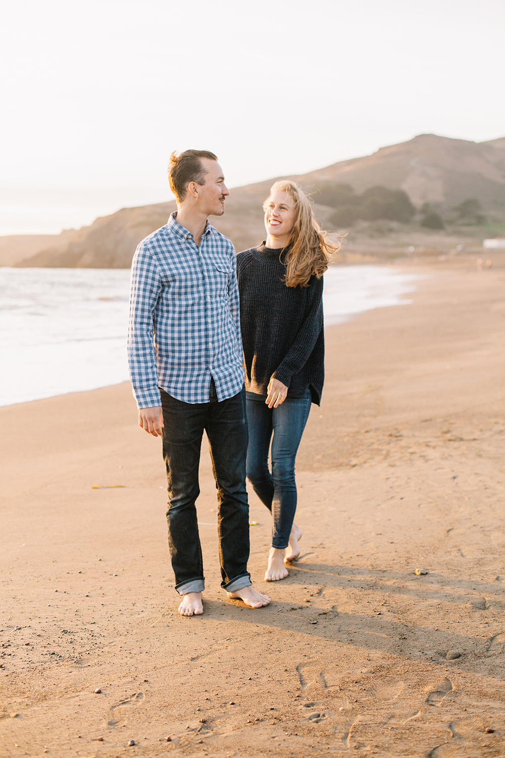 Candid portrait of couple during sunset engagement session at Rodeo Beach in Marin Headlands, California.