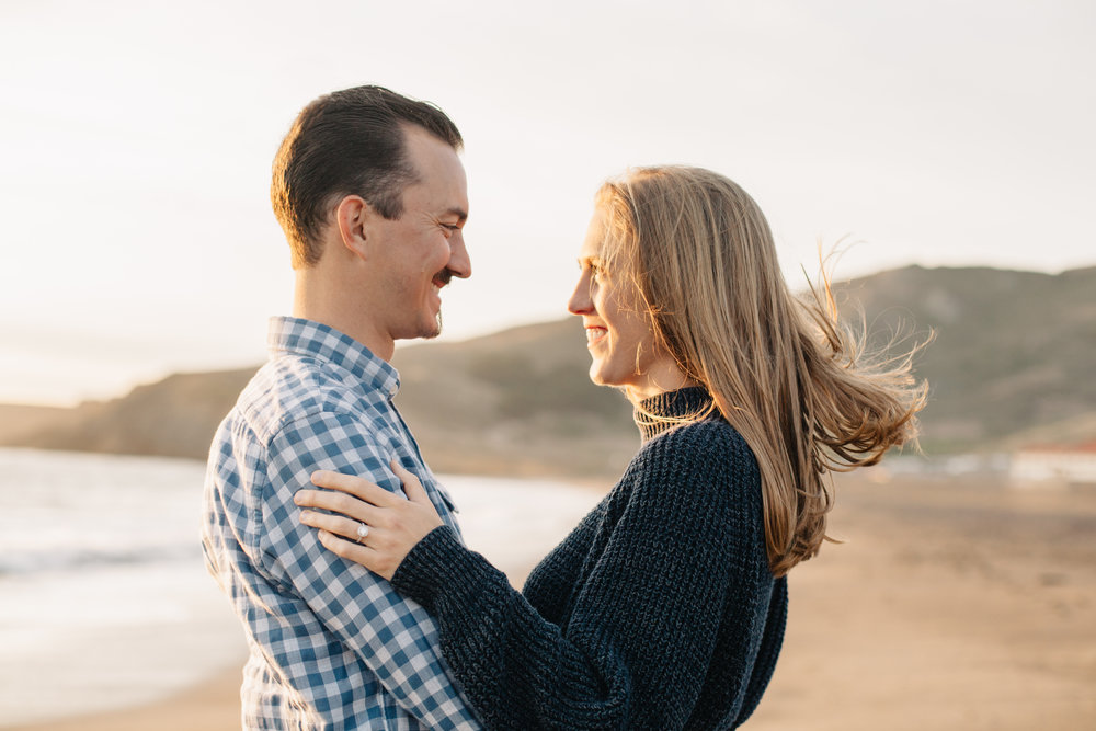 Portrait of couple during their sunset engagement session at Rodeo Beach in Marin Headlands, California.