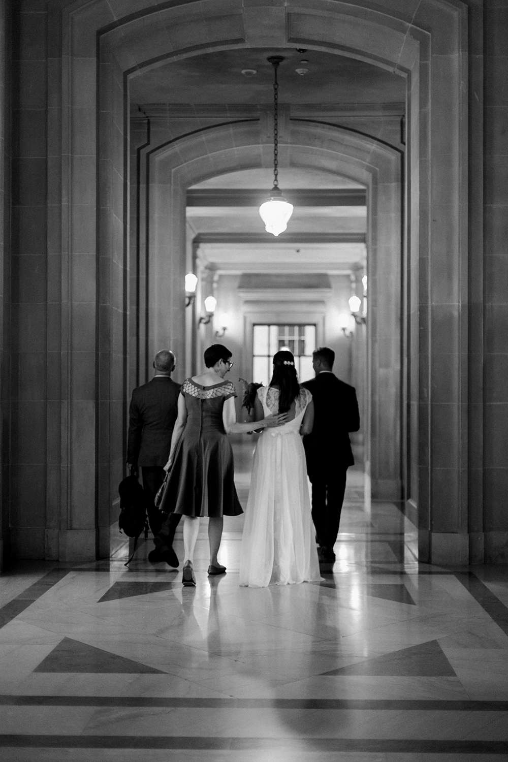 Bride and groom walking towards their ceremony in San Francisco City Hall.