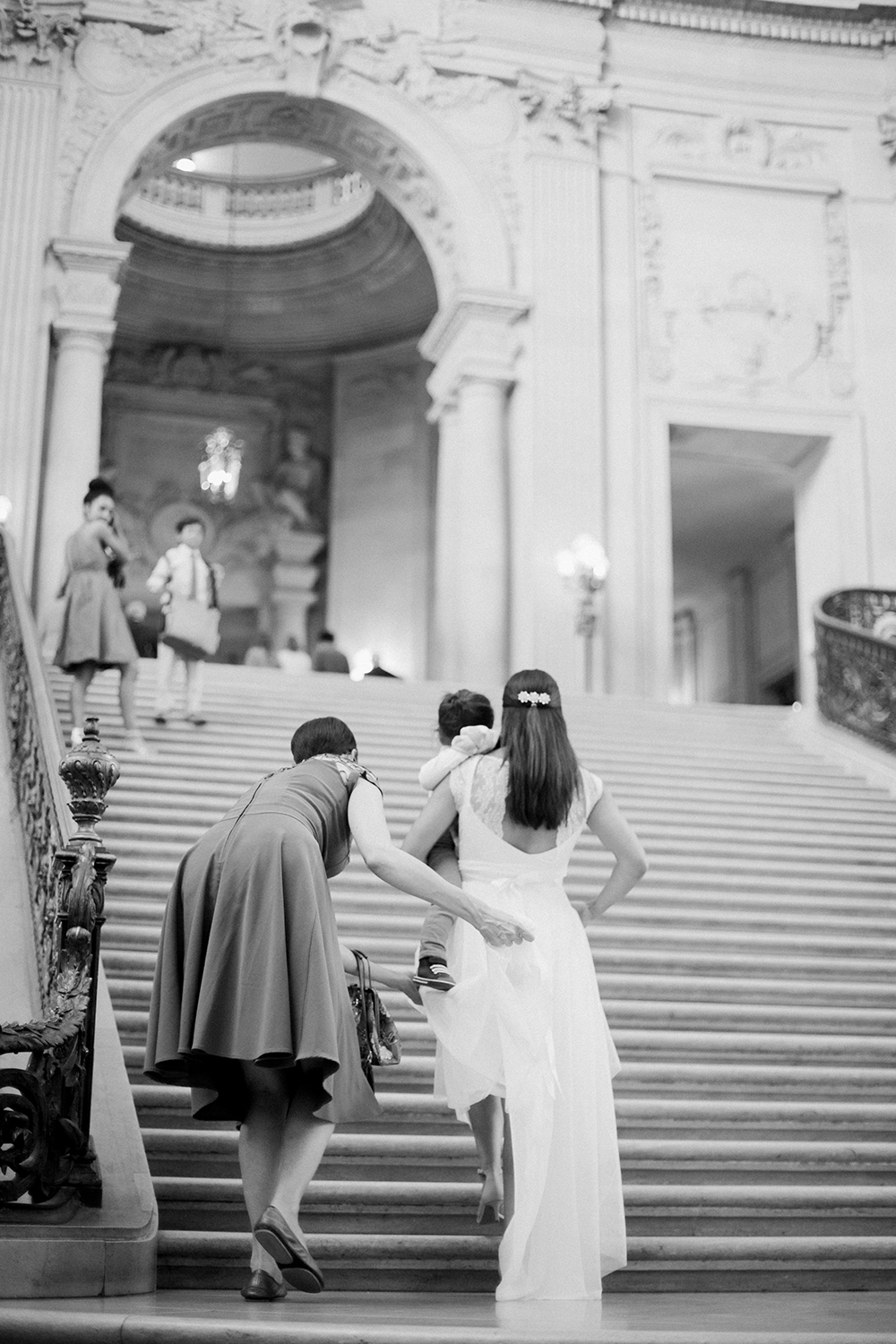 Bride walking up the steps during her wedding in San Francisco City Hall.