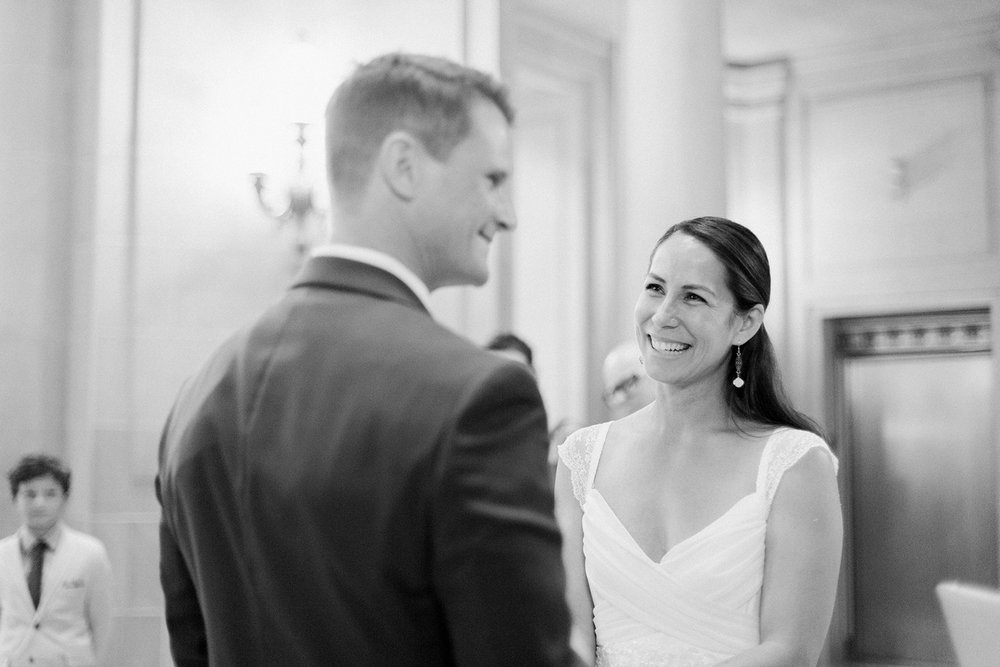 Bride smiling at her groom during their wedding ceremony in San Francisco City Hall.