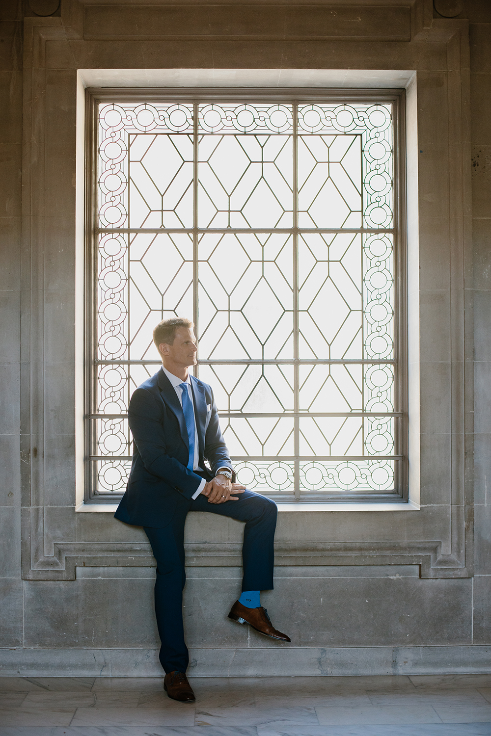 Groom sitting by window during his wedding in San Francisco City Hall.