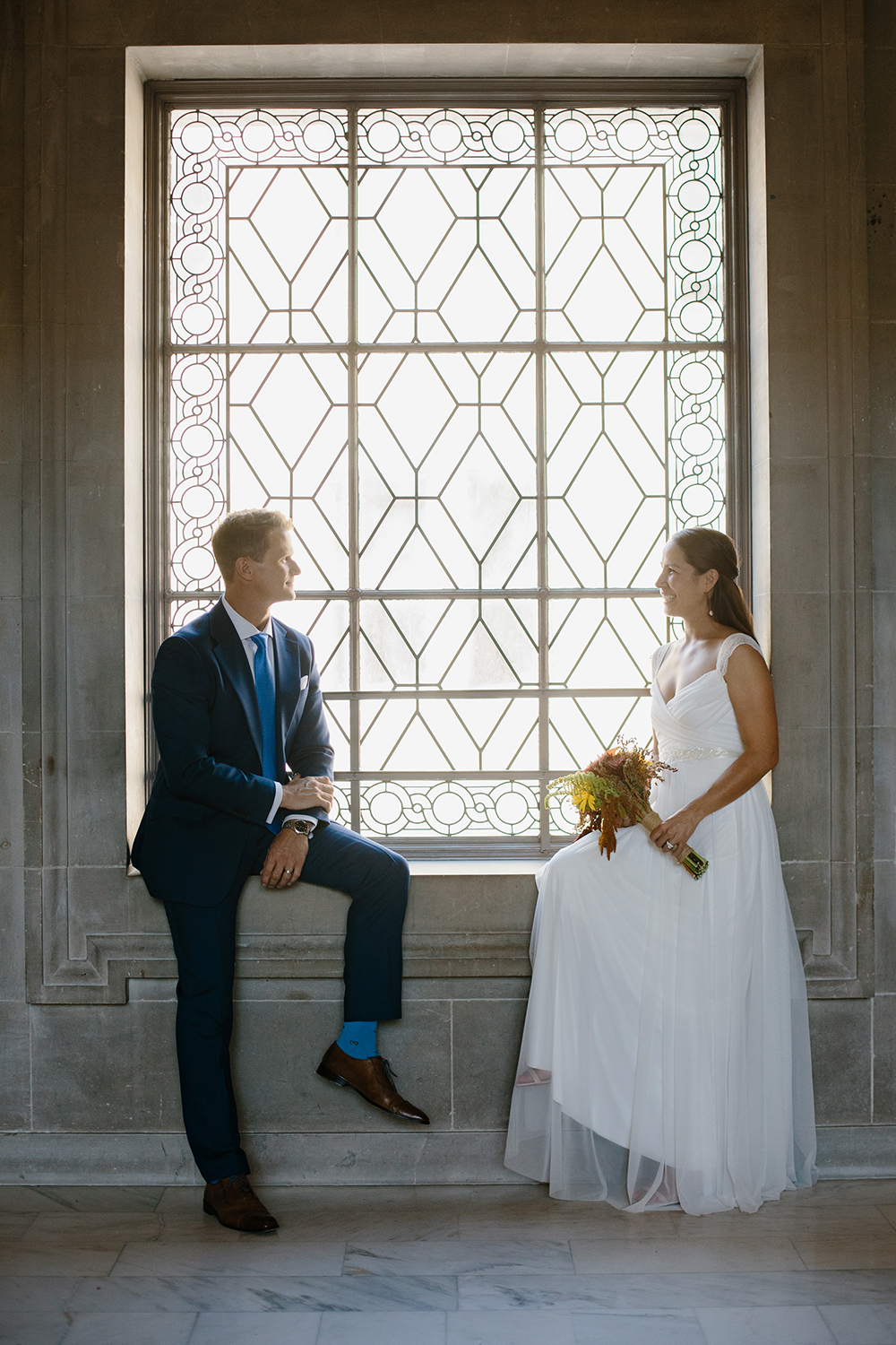 Bride and groom sitting by window after eloping in San Francisco City Hall