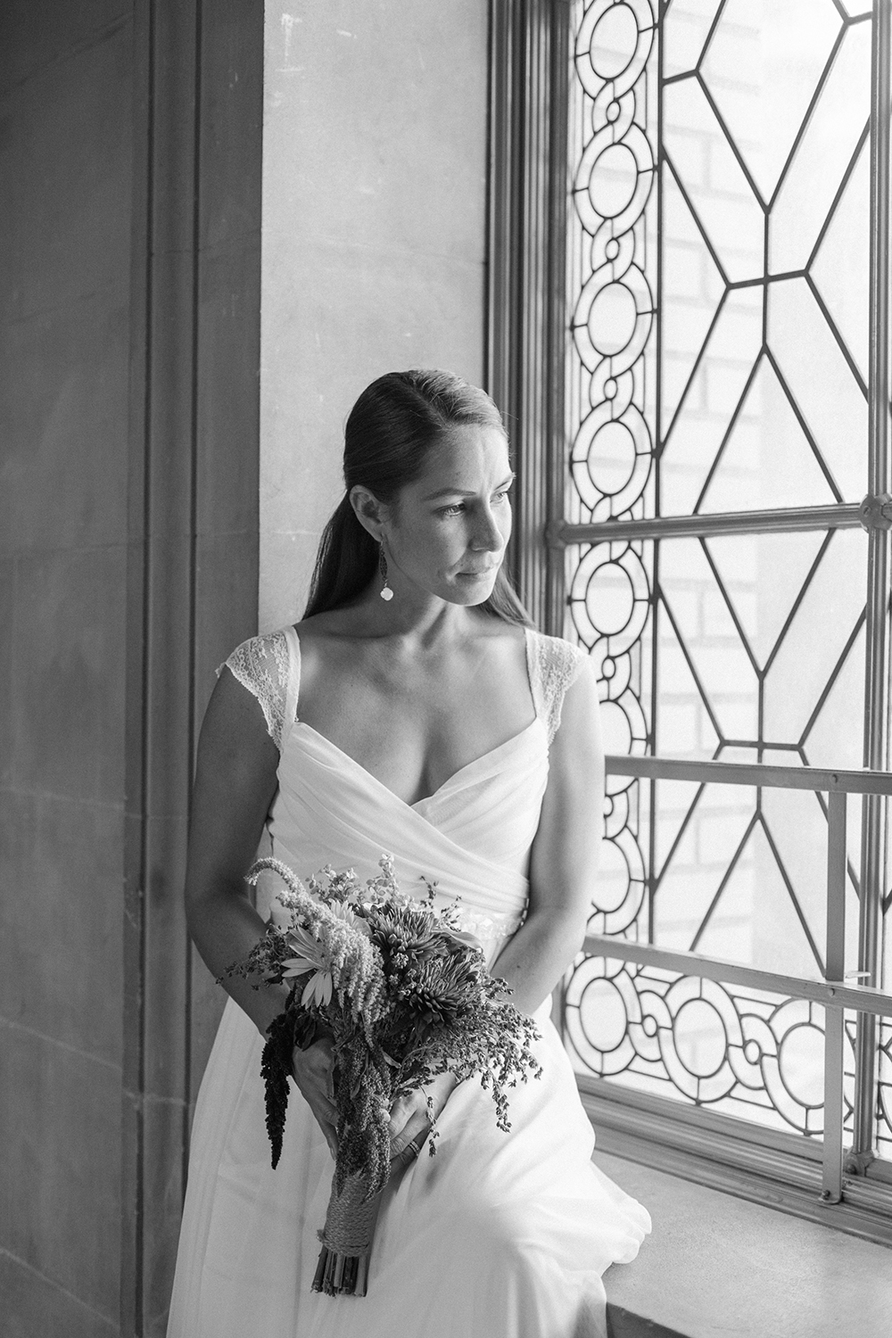 Bride sitting by window after eloping in San Francisco City Hall