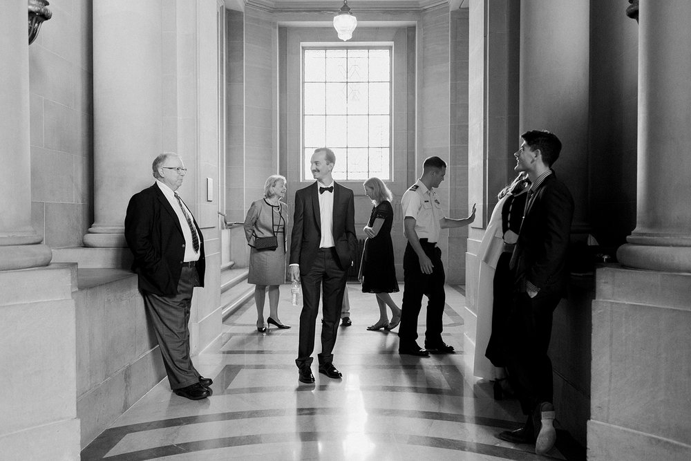 Candid photo of family and groom at wedding in San Francisco City Hall.